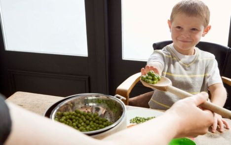 Boy rejecting serving of peas